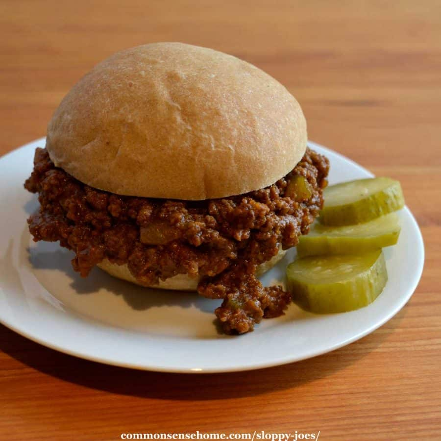 sloppy joe on white plate with pickle slices