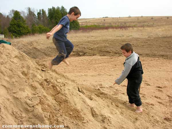 boys playing in sand pile
