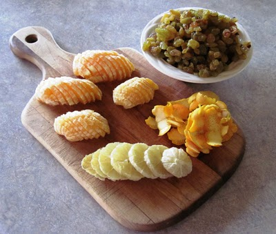 orange and lemon slices and rind on cutting board and bowl of golden raisins for making dandelion wine