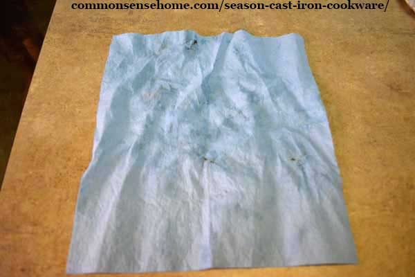 shop towel with excess oil removed during cast iron seasoning