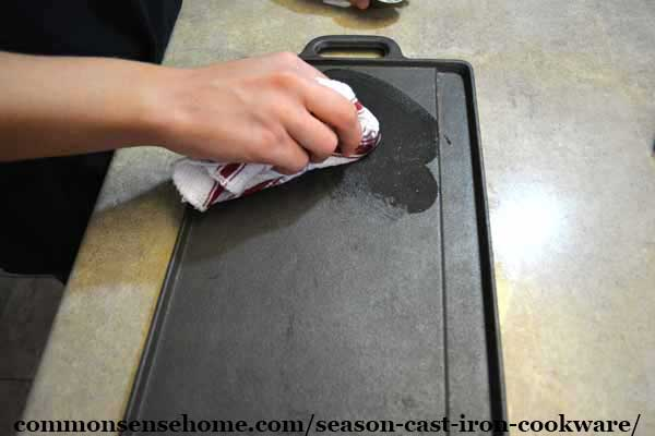applying oil to season a cast iron griddle