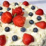 red, white and blue cake decorations for Fourth of July with strawberry roses and blueberries