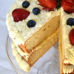 Red, White and Blue Fourth of July Cake with Fresh Berries and Cream Filling on pedestal with one slice removed