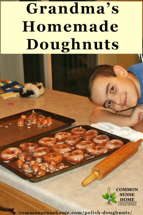 little boy smiling next to homemade doughnuts