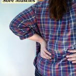 sore muscles in back of woman wearing flannel shirt