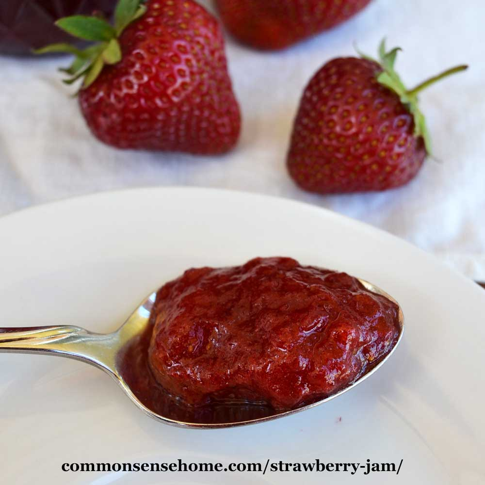 strawberry jam on a spoon on a white plate with strawberries in the background
