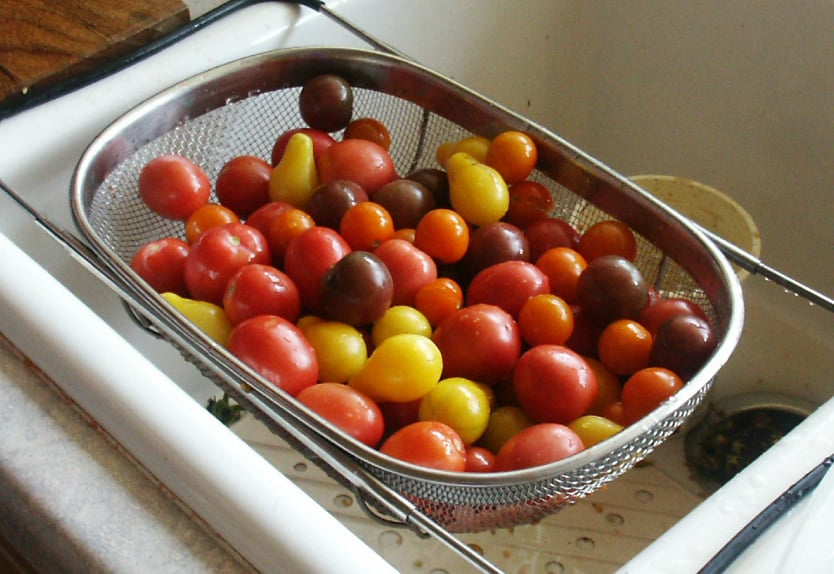 over the sink colander with cherry tomatoes