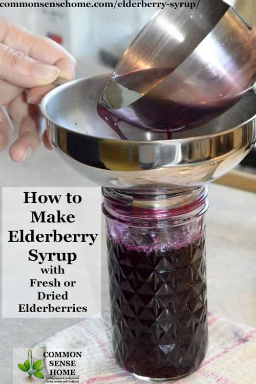 Ladling homemade elderberry syrup into a mason jar