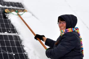 woman cleaning snow from solar panels