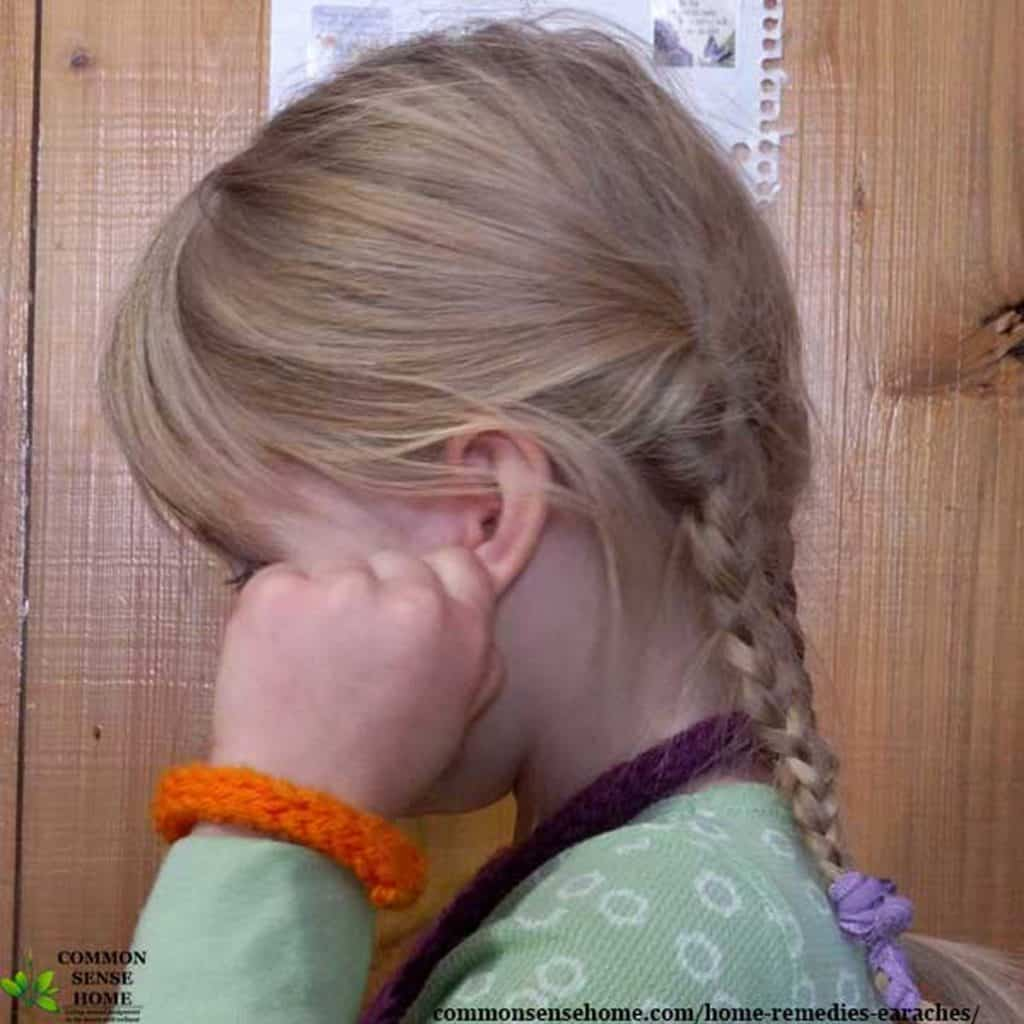 child holding ear in pain