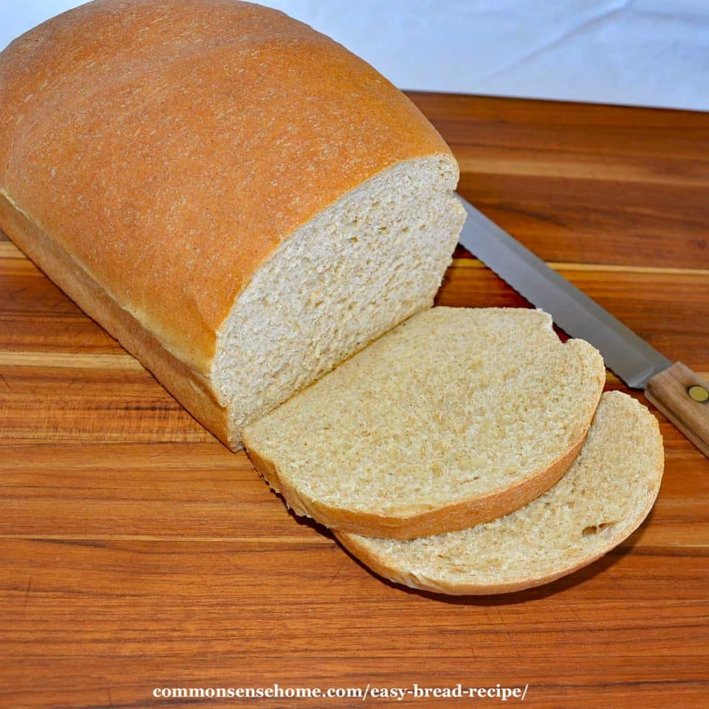 easy bread recipe - loaf of bread with two slices cut off on cutting board