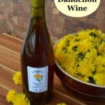 bottle of dandelion wine next to bowl of dandelion flowers