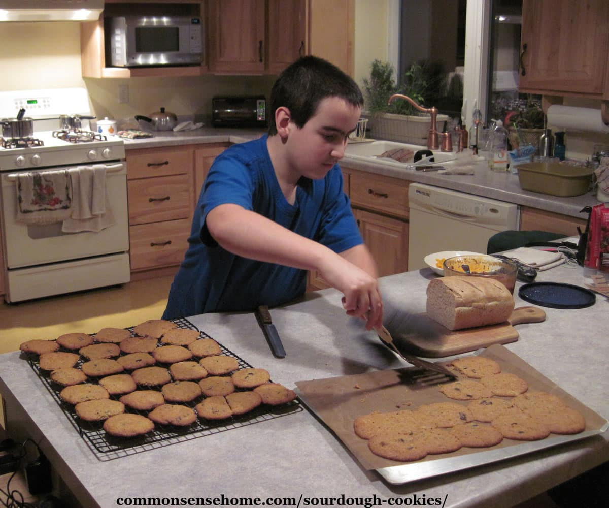 boy removing finished cookies from baking sheet
