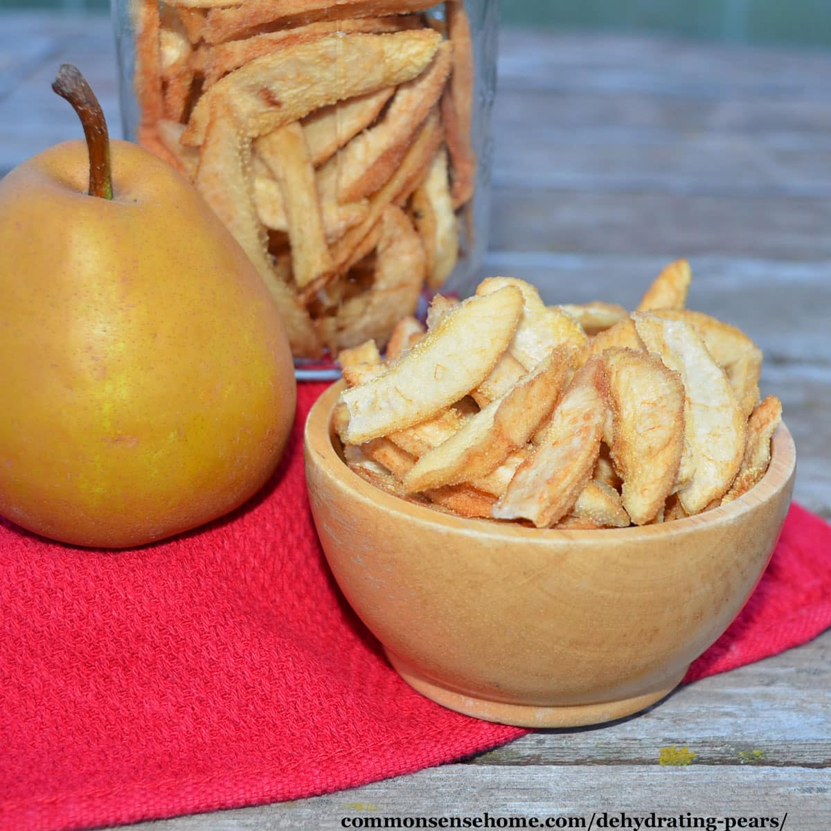 fresh pear and bowl of dehydrated pears
